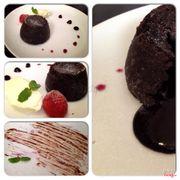 Fondant Chocolate Cake - 60.000 Bánh ngon. Mang rang lúc còn ấm ấm, xắn miếng bánh thì chocolate bên trong chảy ra. Ăn kèm với cream cheese và sốt blueberry thì phải.