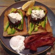 Avocado, ricotto, roasted tomato on toast with a side of a poached egg and bacon