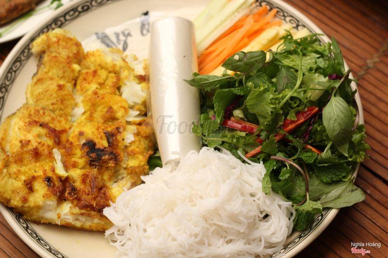 Cá nướng cuốn kèm rau sống, cà rốt, dưa chuột và dứa chấm nước chấm đặc trưng tạo nên hương vị đậm đà khó quên khi thưởng thức tại Ngư Quán